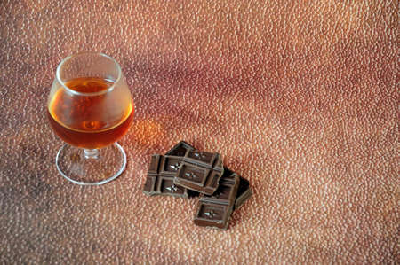 A glass of cognac and a few pieces of chocolate on a brown abstract background. Close-up. Reklamní fotografie