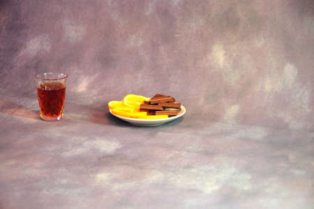 Crystal glass of cognac and a plate with cut lemon and pieces of chocolate on a gray background. Close-up. Reklamní fotografie
