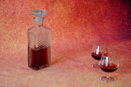 Crystal bottle of cognac and two glasses with a drink on a brown abstract background. Close-up.