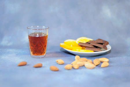 Crystal glass with cognac, next to a plate with lemon slices and chocolate, a handful of nuts in the foreground. Close-up. Reklamní fotografie