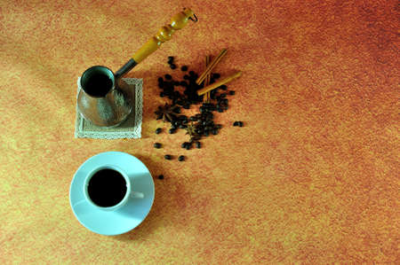 A cup on a saucer with hot coffee, an old-fashioned copper turk and coffee beans on a brown background.