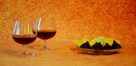 Two glasses with cognac and a plate with lemon slices and chocolate candies on a brown abstract background. Close-up.