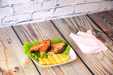 Two grilled pink salmon steaks lie on a white ceramic plate decorated with lemon slices and a lettuce leaf next to a white napkin with cutlery, the whole composition on a wooden table. Close-up. Reklamní fotografie