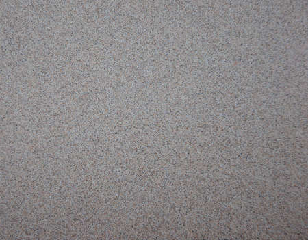 Light gray granite interspersed with black and brown finely divided particles. Close-up.