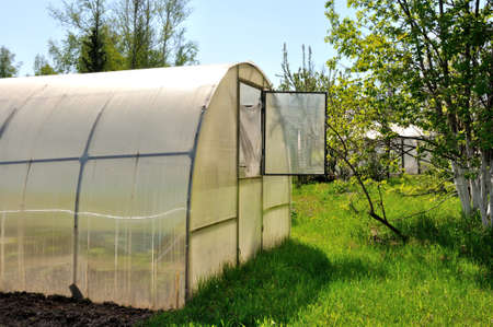 A greenhouse on a metal frame with a polycarbonate roof with an open window on a plot of green grass. Agriculture.