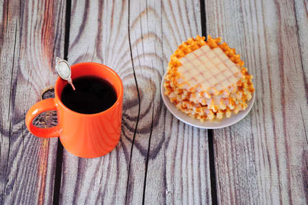 An orange mug with black coffee and a plate with a stack of Parisian waffles with syrups stand on a wooden table. Close-up.