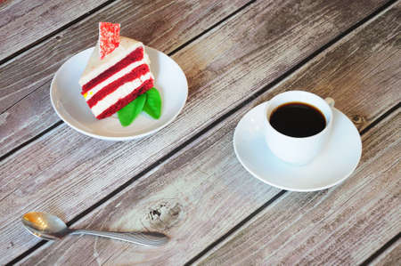 A piece of red velvet cheesecake with a leaf of mint and a cup of fresh cappuccino stands on a wooden table. Close-up. Фото со стока