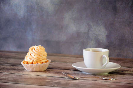 Ceramic cup of black coffee and a shortbread cake basket with cream on a wooden table. Close-up.