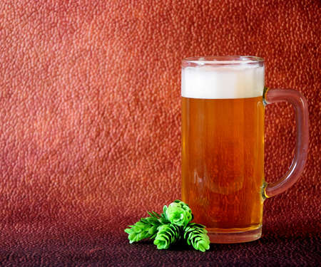 Tall glass mug of light beer with foam and hops stand on a brown abstract background. Close-up. Stok Fotoğraf
