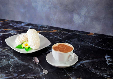Two Bizete cakes with a flower bud on a saucer, a cup of cappuccino and a teaspoon are on a marble blue table. Close-up.