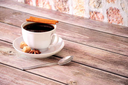 A cup of black coffee on a saucer with anise, cinnamon and pieces of cane sugar. Close-up. Zdjęcie Seryjne