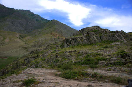 A rock massif in a picturesque valley surrounded by dry hills. Altai mountains, Siberia, Russia.