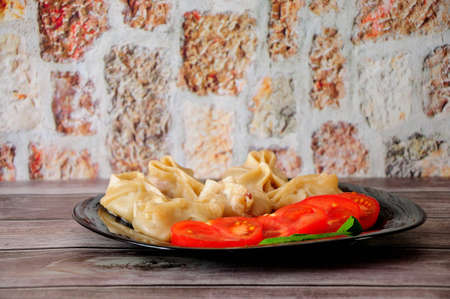 A plate with fresh manti, tomato and a leaf of salad stands on a wooden table. Close-up.