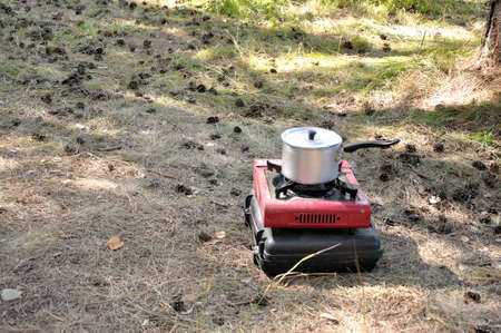 An aluminum saucepan with a closed lid stands on a camping gas stove on the sand in the forest. Karakansky Bor, Novosibirsk Region.