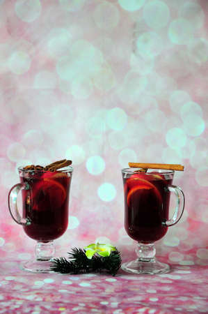 Two glasses of hot red wine with cinnamon and anise are on a pink background decorated with a branch of pine needles and a vanilla flower. Vertical positioning.