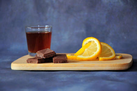 A glass of cognac, chocolate wedges and slices of sliced lemon on a wooden board stand against a dark gray background. Close-up. Stockfoto