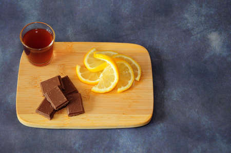 Wooden board with lemon slices, chocolate pieces and a glass of cognac on a gray background. Close-up. Stockfoto