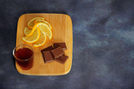 Wooden board with a glass of cognac, chocolate wedges and lemon slices on a gray background. Close-up.