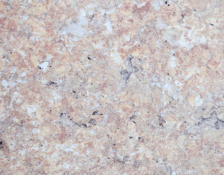 Pale pink marble interspersed with black and gray colors, close-up of a smooth polished natural stone surface. Background, texture.
