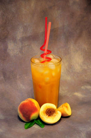 A tall glass of orange juice with ice and ripe peaches nearby on a gray abstract background. Vertical positioning.