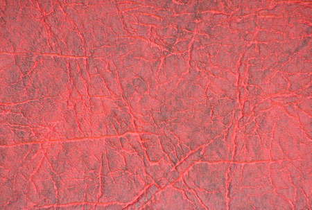 A fragment of genuine leather with folds, artificially dyed in burgundy color. Background, pattern, texture.