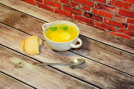 Deep round plate with handles of fresh chicken broth with egg, spoon and two slices of white bread on a wooden table against a red brick wall. Close-up.