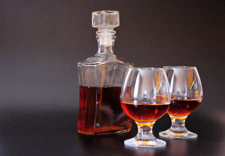Glass bottle with a lid and two glasses with cognac on a black background. Close-up.