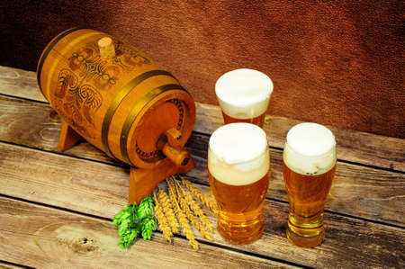 Three glasses of light beer, a wooden keg, hops and malt on a wooden table. Close-up.