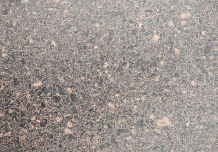 Natural black granite with small orange splashes, close-up of polished flat stone surface. Background, pattern, texture.