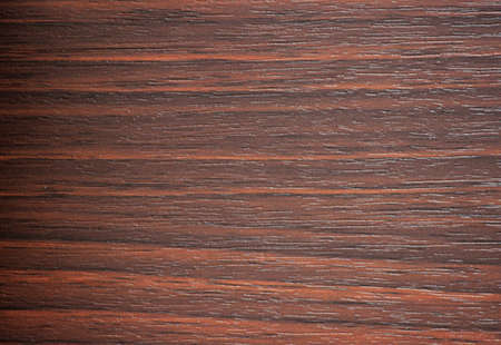 Red walnut, natural dark wood with a striped pattern close-up. Background, pattern, texture.
