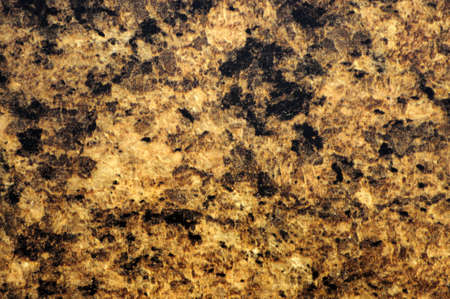 Natural orange granite with small black inclusions, close-up of polished flat stone surface. Background, pattern, texture.