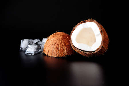 Broken coconut with melted ice cubes on a black background. Close-up.