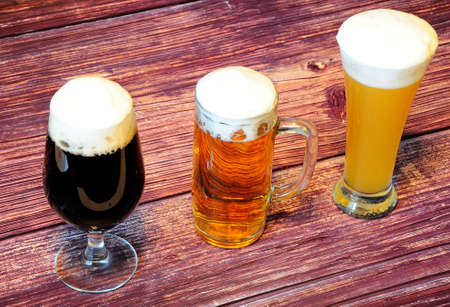 Three different glasses with different types of beer, light, dark and wheat on a wooden table. Close-up.