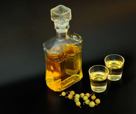 Homemade green gooseberry liqueur in a bottle and two glasses on a black background, next to a handful of ripe berries. Close-up.