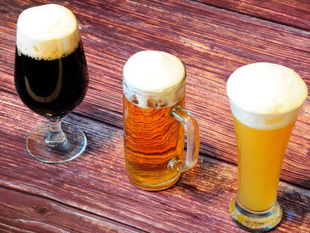 Beer, wheat, light and dark, in different glasses, stand in a row on a dark wooden table. Close-up. Standard-Bild