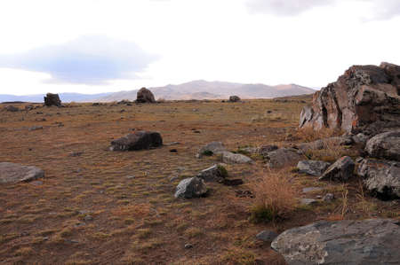 Stone ruins of an ancient observatory in the center of the steppe at the foot of the mountains in early autumn. Tarkhatinsky megalithic complex, Altai, Siberia, Russia. Standard-Bild