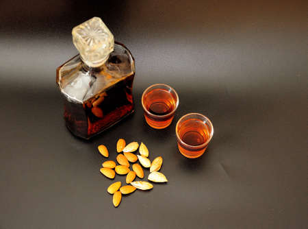 Amaretto, a migdal liqueur in two glasses and a glass bottle on a black background. Close-up.