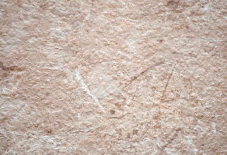 Pink onyx, rough-cut surface of natural stone with small inclusions, close-up. Background, pattern, texture.