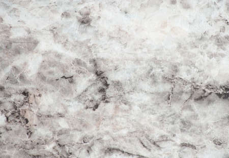 Snow-white marble, polished surface of natural stone with fine veins and black blotches. Background, pattern, texture.