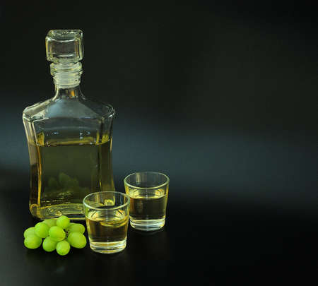 Grappa, a strong alcohol poured into two glasses and a glass bottle on a black background, next to a bunch of ripe white grapes. Close-up. Standard-Bild