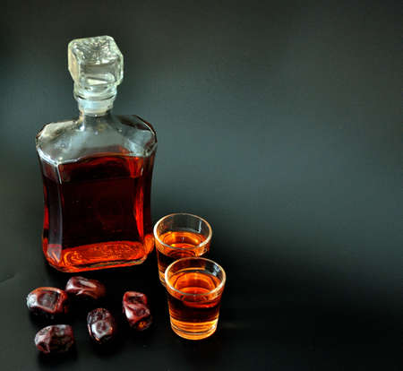 Date liqueur, homemade strong alcohol poured into two glasses and a glass bottle on a black background, ripe fruits next to it. Close-up.