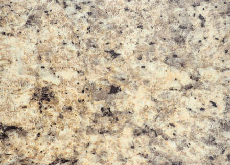 Pale beige granite with small black and orange blotches, close-up of polished natural stone surface. Background, pattern, texture.