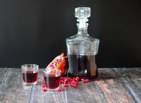 Pomegranate liqueur in a bottle and two glasses stands on a wooden table against a black wall, next to it is a broken ripe fruit with a scattering of grains. Close-up.