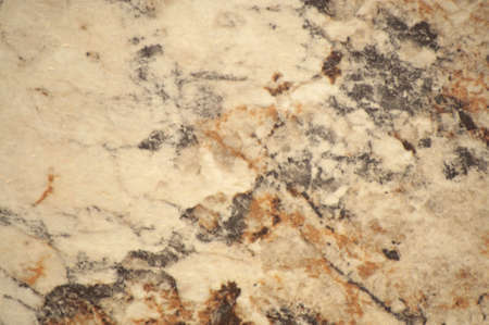 Pale brown marble with fine orange blotches and black-gray veins. Background, pattern, texture.