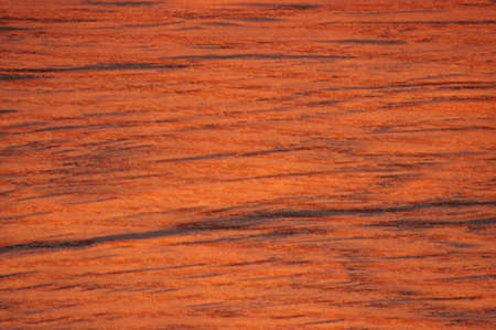 Mahogany, a natural red wood surface with deep black natural stripes. Background, pattern, texture.