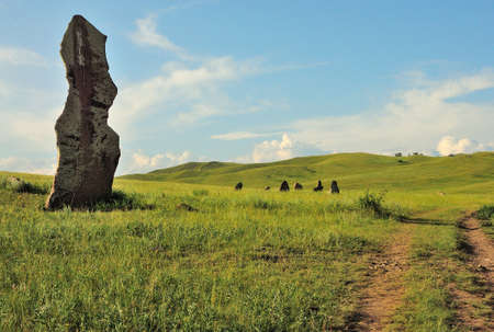 A tall stone menhir stands at the side of a field road that runs through the hilly steppe. Safronovskie kurgans, Khakassia, Siberia, Russia.