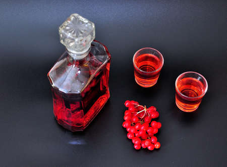 Viburnum homemade liqueur, a low-alcohol drink in a glass bottle and two glasses on a black background, next to a branch with ripe bright red berries. Close-up.