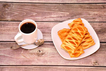 Three puffs with apple filling on a white ceramic plate and a cup of hot black coffee stand on a wooden table. Close-up. Standard-Bild