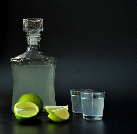 Lime-based liqueur, strong alcohol in a bottle and two glasses on a black background, sliced ripe citrus next to it. Close-up.