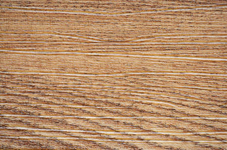 Natural pine artificially tinted in a dark color with a wavy pattern on the cut. Background, pattern, texture.